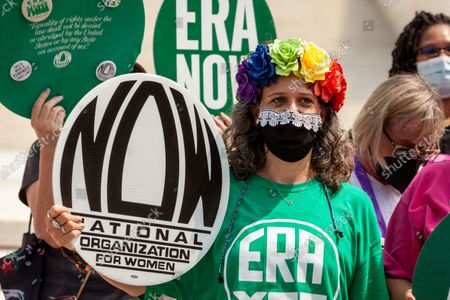 A demonstrator wears a rainbow band of flowes and a mask with lace along the top, reminiscent of Justice Ruth Bader Ginsburg's robe, at a rally to pass the Equal Rights Amendment (ERA) at the Supreme Court.  The amendment would prohibit discrimination on the basis of sex, which would require equal pay for women, among many other changes.  The required 38 states have ratified the amendment, but, unlike other constitutional amendments, a time limit was placed on the ERA, which has now expired.  ERA proponents are pressuring Congress to extend the time limit.