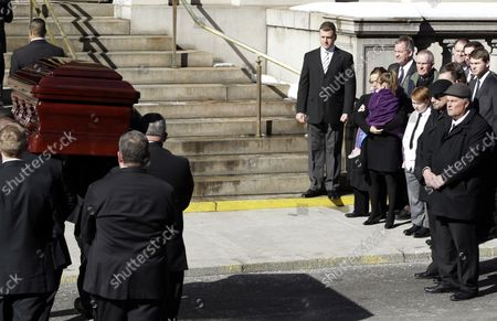 Family Members and mourners watch the casket containing the remains of actor Philip Seymour Hoffman carried up the stairs to his funeral at St. Ignatius Church on Manhattan's Upper East Side in New York City on February 7, 2014. Hoffman, 46, was found dead Sunday of an apparent heroin overdose in his apartment. He leaves behind his partner of 15 years, Mimi O'Donnell, and their three children.