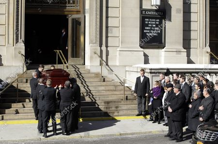 Stock Photo of Family Members and mourners watch the casket containing the remains of actor Philip Seymour Hoffman carried up the stairs to his funeral at St. Ignatius Church on Manhattan's Upper East Side in New York City on February 7, 2014. Hoffman, 46, was found dead Sunday of an apparent heroin overdose in his apartment. He leaves behind his partner of 15 years, Mimi O'Donnell, and their three children.
