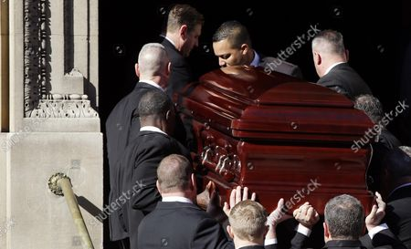 Stock Picture of Pallbearers carry the casket containing the remains of actor Philip Seymour Hoffman up the stairs to his funeral at St. Ignatius Church on Manhattan's Upper East Side in New York City on February 7, 2014. Hoffman, 46, was found dead Sunday of an apparent heroin overdose in his apartment. He leaves behind his partner of 15 years, Mimi O'Donnell, and their three children.
