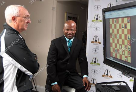 Chess grandmaster and ESPN Chess commentator Maurice Ashley (R) and Chess Club and Scholastic Center of Saint Louis founder Rex Sinquefield discuss moves of participants in Round 2 of the U.S. Chess Championship at the Chess Club of Saint Louis in St. Louis on May 9, 2014. The championships run through May 20.