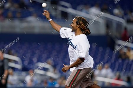 """Cuban singer Yotuel Romero throws out a ceremonial first pitch before a baseball game between the Miami Marlins and the Cincinnati Reds, in Miami. Romero is one of the co-writers of the song """"Patria y Vida"""