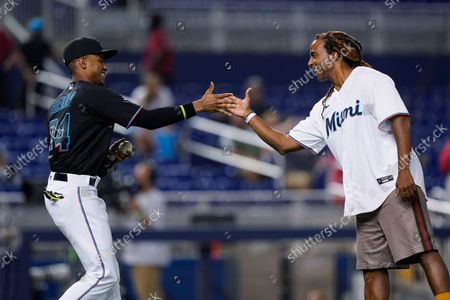 """Cuban singer Yotuel Romero, right, is congratulated by Miami Marlins center fielder Magneuris Sierra (34) after Romero threw out a ceremonial first pitch before a baseball game between the Marlins and the Cincinnati Reds, in Miami. Romero is one of the co-writers of the song """"Patria y Vida"""