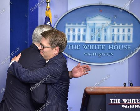 White House Press Secretary Jay Carney (R) embraces Chief of Staff Denis McDonough at the conclusion of Carney's last press briefing, June 18, 2014, in Washington, DC.
