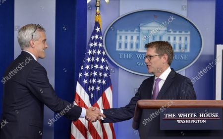White House Press Secretary Jay Carney (R) shakes hands with Chief of Staff Denis McDonough at the conclusion of Carney's last press briefing, June 18, 2014, in Washington, DC.