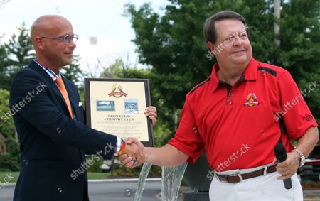 Greg Marecek, President of the St. Louis Spoirts Hall of Fame (R) presents Glen Echo Country Club general manager Rob Stewart with an induction placque during ceremonies at the club in St. Louis on June 26, 2014. Glen Echo was the site of golf during the 1904 Olympics, held in St. Louis and was the last time golf was played in an Olympics. In 2016 golf will return as an olympic event in Rio.