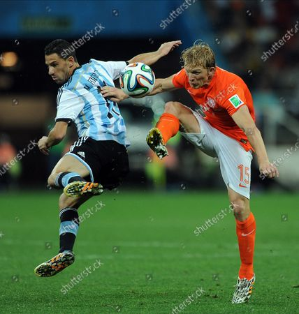 Dirk Kuyt of the Netherlands competes with Maxi Rodriguez (L) of Argentina during the 2014 FIFA World Cup Semi Final match at the Arena Corinthians in Sao Paulo, Brazil on July 09, 2014.