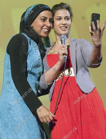 """Stock Image of British-Canadian author and filmmaker Zarqa Nawaz (L) and host and actress Anita Majumdar take a selfie after Nawaz gives a talk and Q & A at Simon Fraser University's Goldcorp Centre for the Performing Arts introducing her new book """"Laughing All the Way to the Mosque"""" in Vancouver, British Columbia, June 9, 2014. Best known for creating the hit television series """"Little Mosque on the Prairie"""" Nawaz hopes to put the fun back into fundamentalism which is the theme of her talk at the Indian Summer Festival."""