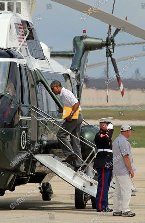 Stock Picture of President Barack Obama boards Marine One en route Camp David in Maryland following a round of golf at Joint Base Andrews near Washington, D.C., on August 2, 2014.