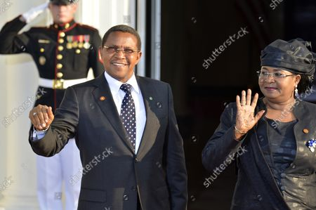 Tanzania's President Jakaya Mrisho Kikwete and First Lady Salma Kikwete greet the press as they arrive at the White House for a State Dinner on behalf of the US-Africa Leaders Summit, August 5, 2014, in Washington, DC. Nearly 50 heads of state and government from Africa are attending the summit to advance business, agriculture, development and infrastructure interests on the continent.