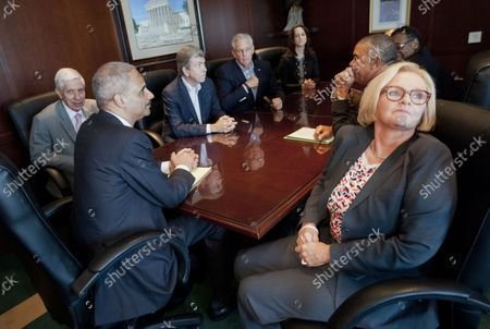 Attorney General Eric Holder, left, during his meeting at the US Attorney's office in St. Louis, Mo., Wednesday, Aug. 20, 2014. Sitting with clockwise from the far left, Richard Callahan, US Attorney for the Eastern District of Missouri, Sen. Roy Blunt, R-Mo., Missouri Gov. Jay Nixon, Acting Assistant Attorney General for Civil Rights Molly Moran, Rep. Emanuel Cleaver, D-Mo., Rep. Lacy Clay, D-Mo., and Sen. Claire McCaskill, D-Mo.