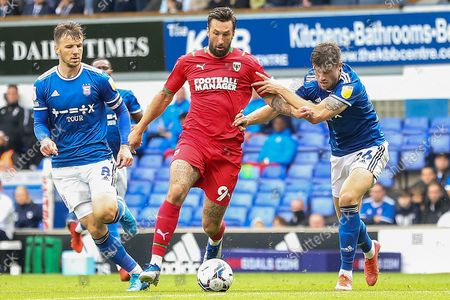 Stock Picture of AFC Wimbledon forward Ollie Palmer (9) battles with Ipswich Town defender Cameron Burgess (26) and Ipswich Town midfielder Lee Evans (8) during the EFL Sky Bet League 1 match between Ipswich Town and AFC Wimbledon at Portman Road, Ipswich