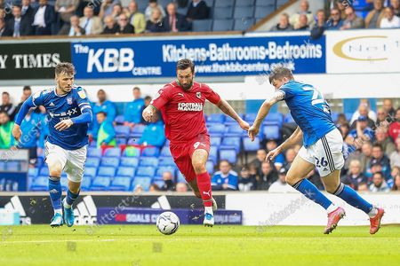 Stock Photo of AFC Wimbledon forward Ollie Palmer (9) battles with Ipswich Town defender Cameron Burgess (26) and Ipswich Town midfielder Lee Evans (8) during the EFL Sky Bet League 1 match between Ipswich Town and AFC Wimbledon at Portman Road, Ipswich