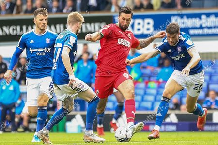 Stock Image of AFC Wimbledon forward Ollie Palmer (9) battles with Ipswich Town defender Cameron Burgess (26), Ipswich Town midfielder Lee Evans (8) and Ipswich Town defender Hayden Coulson (27) during the EFL Sky Bet League 1 match between Ipswich Town and AFC Wimbledon at Portman Road, Ipswich