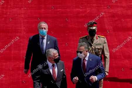 Photo released by the Iraqi Prime Minister Media Office shows Iraqi Prime Minister Mustafa al-Kadhimi, right, as he welcomes Jordan's King Abdullah II before the Baghdad Conference for Cooperation and Partnership in Baghdad