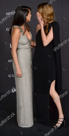 Actress Selena Gomez (L) and model Cara Delevingne, both 22, cozy up as they pose for photos during the fourth annual LACMA Art + Film gala honoring Barbara Kruger and  Quentin Tarantino in Los Angeles on November 1, 2014. Gomez wore a silver gown with plunging neckline and sequin and beaded detail, while Delevingne donned a one-shoulder black dress with asymmetrical hem and sequin lining.