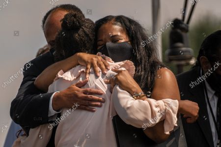 """Yolanda Renee King, center, receives a hug from Martin Luther King III, left and Andrea Waters King, right after speaking on the National Mall during the """"March on Washington"""" on the 58th anniversary of the Rev. Martin Luther King Jr.'s """"I Have a Dream"""" speech, in Washington, DC on Saturday, August 28, 2021. Voting rights advocates are demanding federal legislation to protect and expand access to the ballot."""