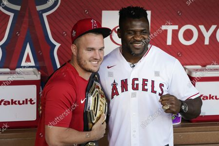 Los Angeles Angels' Mike Trout, left, and UFC fighter Francis Ngannou pause for photos before the Angels' baseball game against the San Diego Padres in Anaheim, Calif