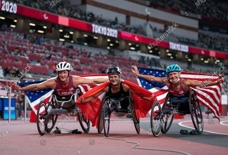 Silver Medallist Tatyana McFadden USA, Gold Medallist Manuela Schaer SUI and Bronze Medallist Susannah Scaroni USA pose with their national flags after the Women's Athletics 800m - T54 Final at the Olympic Stadium. Tokyo 2020 Paralympic Games, Tokyo, Japan, Sunday 29 August 2021. Photo: OIS/Bob Martin. Handout image supplied by OIS/IOC