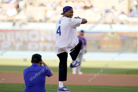Rapper YG throws the ceremonial first pitch during before a baseball game between the Los Angeles Dodgers and the Colorado Rockies, in Los Angeles