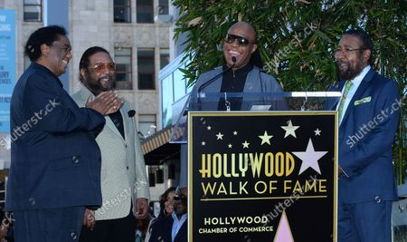 Songwriters Lamont Dozier, Eddie Holland and Brian Holland (L-R) react to comments by Stevie Wonder (C) during an unveiling ceremony honoring them with the 2,543rd star on the Hollywood Walk of Fame in Los Angeles on February 13, 2015.
