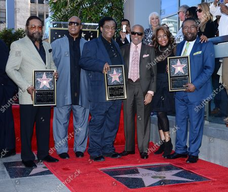 Songwriters Eddie Holland, Lamont Dozier and Brian Holland (L-R) hold replica plaques during an unveiling ceremony honoring them with the 2,543rd star on the Hollywood Walk of Fame in Los Angeles on February 13, 2015. Posing with the songwriting trio are Stevie Wonder, Barry Gordy and Mary Wilson (L-R).