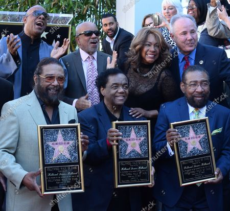 Songwriters Eddie Holland, Lamont Dozier and Brian Holland (L-R) hold replica plaques during an unveiling ceremony honoring them with the 2,543rd star on the Hollywood Walk of Fame in Los Angeles on February 13, 2015. Joining them are singer/songwriter Stevie Wonder, record producer Berry Gordy, singer Mary Wilson and Councilman Tom LaBonge (L-R, rear).