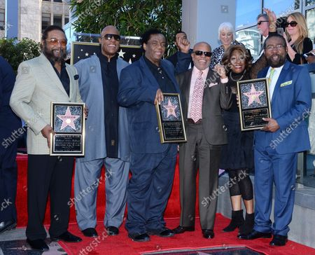 Stock Image of Songwriters Eddie Holland, Lamont Dozier and Brian Holland (L-R) hold replica plaques during an unveiling ceremony honoring them with the 2,543rd star on the Hollywood Walk of Fame in Los Angeles on February 13, 2015. Posing with the songwriting trio are Stevie Wonder, Barry Gordy and Mary Wilson (L-R).