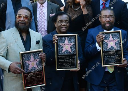 Songwriters Eddie Holland, Lamont Dozier and Brian Holland (L-R) hold replica plaques during an unveiling ceremony honoring them with the 2,543rd star on the Hollywood Walk of Fame in Los Angeles on February 13, 2015.