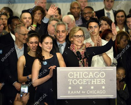 """Chicago Mayor Rahm Emanuel (C) waves to supporters as he stands on stage with his wife Amy Rule, son Zachariah (R) and daughters Leah and Ilana at a rally at the Plumbers Local Union 130 hall following the mayoral run-off election in Chicago on April 7, 2015. Emanuel defeated opponent Jesus """"Chuy"""" Garcia in the first runoff since Chicago switched to non-partisan elections 20 years ago."""