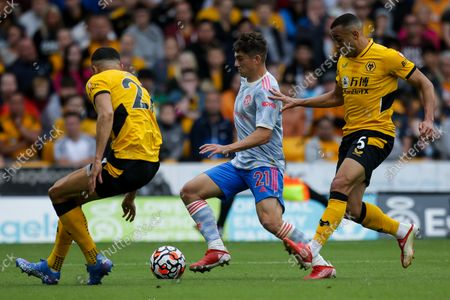 Daniel James of Manchester United takes on Marcal and Romain Saiss of Wolverhampton Wanderers