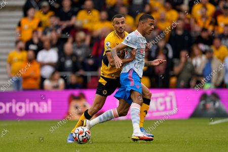 Romain Saiss (L) of Wolverhampton and Mason Greenwood (R) of Manchester United in action during the English Premier League soccer match between Wolverhampton Wanderers and Manchester United in Wolverhampton, Britain, 29 August 2021.
