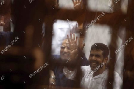 Top Egyptian Muslim Brotherhood leaders Essam el-Erian (L) and  gesture with fellow accused from the defendents cage during their trial alongside 14 others, including former Islamist president Mohamed Morsi, at a court in the capital, Cairo, Egypt, on April 21, 2015.  An Egyptian court sentenced Morsi to 20 years in prison without parole on Tuesday for the killing of protesters in December 2012.