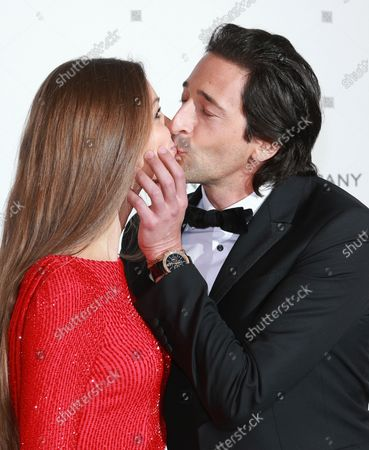 Lara Lieto (L) and Adrian Brody share a kiss at the 22nd amfAR Cinema Against AIDS 2015 gala at the Hotel du Cap-Eden-Roc in Antibes, France on May 21, 2015.  The event, held each year during the annual Cannes Film Festival, raises funds for AIDS research.