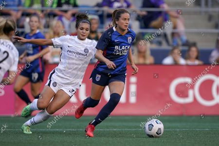 Reign defender Lauren Barnes, right, is challenged by Portland Thorns FC forward Sophia Smith, left, during the second half of an NWSL soccer match, in Seattle