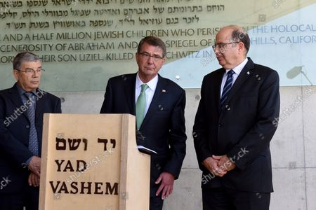 Israeli Defense Minister Moshe Ya'alon (R) watches US Secretary of Defense Ashton Carter sign the guestbook outside the Children's Memorial of the Yad Vashem Holocaust Museum that commemorates the six million Jews killed by the German Nazis during World War II, in Jerusalem, Israel, July 21, 2015.  Carter is visiting Israel to ease concerns over the nuclear deal with Iran.