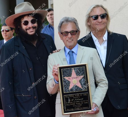 Music pioneer and recording engineer Al Schmitt holds a replica plaque flanked by musicians Don Was (L) and Joe Walsh during an unveiling ceremony honoring him with the 2,557th star on the Hollywood Walk of Fame in Los Angeles on August 13, 2015.