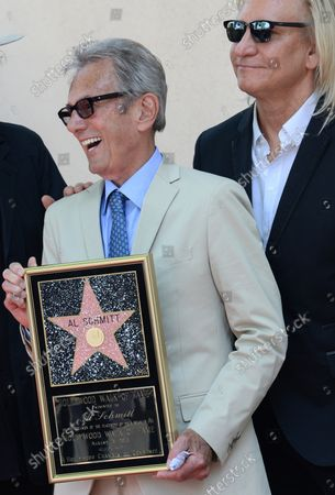Music pioneer and recording engineer Al Schmitt holds a replica plaque during an unveiling ceremony honoring him with the 2,557th star on the Hollywood Walk of Fame in Los Angeles on August 13, 2015.  Looking on at rear is musician Joe Walsh.