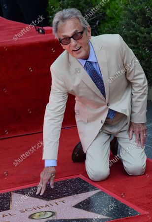 Music pioneer and recording engineer Al Schmitt touches his star during an unveiling ceremony honoring him with the 2,557th star on the Hollywood Walk of Fame in Los Angeles on August 13, 2015.