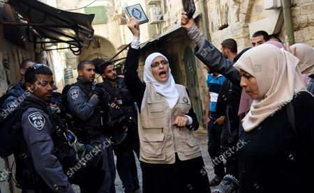 Israeli border police guard Muslim women, from the Mourabitat group, as they shout slogans and hold the Koran, Islam's holy book,  at a protest against Jewish groups visiting the Al-Aqsa Mosque compound and for being banned from their holy site in the Old City of Jerusalem, September 22, 2015. Israeli Defense Minister Moshe Ya'alon outlawed the group of women and issued an order to forbid the Mourabitat group to enter the compound in Jerusalem's Old City that Muslim's call the Noble Sanctuary, or Al-Aqsa, and the Jews call the Temple Mount.