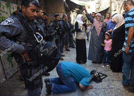 A Muslim man prays on the street between Israeli border police and Muslim women, from the Mourabitat group, as they shout slogans and hold the Koran, Islam's holy book,  at a protest against Jewish groups visiting the Al-Aqsa Mosque compound and for being banned from their holy site in the Old City of Jerusalem, September 22, 2015. Israeli Defense Minister Moshe Ya'alon outlawed the group of women and issued an order to forbid the Mourabitat group to enter the compound in Jerusalem's Old City that Muslim's call the Noble Sanctuary, or Al-Aqsa, and the Jews call the Temple Mount.