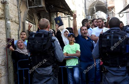 Israeli border police guard Muslim women, from the Mourabitat group, and their supporters, as they shout slogans and hold the Koran, Islam's holy book,  at a protest against Jewish groups visiting the Al-Aqsa Mosque compound and for being banned from their holy site in the Old City of Jerusalem, September 22, 2015. Israeli Defense Minister Moshe Ya'alon outlawed the group of women and issued an order to forbid the Mourabitat group to enter the compound in Jerusalem's Old City that Muslim's call the Noble Sanctuary, or Al-Aqsa, and the Jews call the Temple Mount.