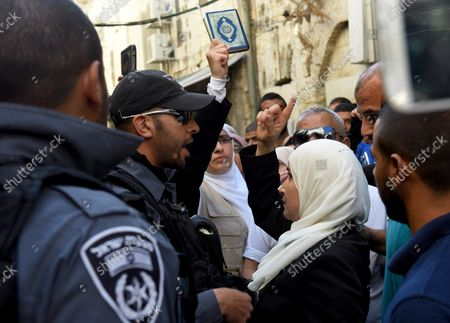 An Israeli border police confronts a Muslim woman, from the Mourabitat group, at a protest against Jewish groups visiting the Al-Aqsa Mosque compound and for being banned from their holy site in the Old City of Jerusalem, September 22, 2015. Israeli Defense Minister Moshe Ya'alon outlawed the group of women and issued an order to forbid the Mourabitat group to enter the compound in Jerusalem's Old City that Muslim's call the Noble Sanctuary, or Al-Aqsa, and the Jews call the Temple Mount.