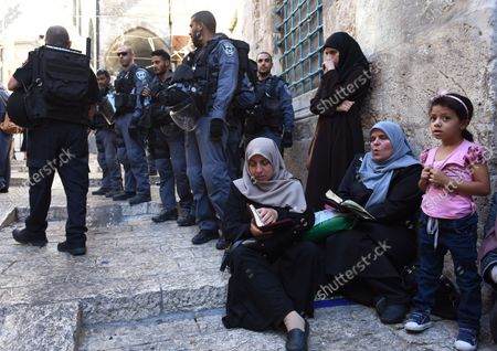 Israeli border police guard Muslim women, from the Mourabitat group, as they read from the Koran, Islam's holy book,  at a protest against Jewish groups visiting the Al-Aqsa Mosque compound and for being banned from their holy site in the Old City of Jerusalem, September 22, 2015. Israeli Defense Minister Moshe Ya'alon outlawed the group of women and issued an order to forbid the Mourabitat group to enter the compound in Jerusalem's Old City that Muslim's call the Noble Sanctuary, or Al-Aqsa, and the Jews call the Temple Mount.