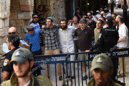 Israeli settlers chant, and dance after leaving the Temple Mount, or Al-Aqsa Mosque compound in Jerusalem's Old City, September 22, 2015.Israeli border police guard  Muslim women, from the Mourabitat group, not seen, as they shout slogans and hold the Koran, Islam's holy book,  at a protest against Jewish groups visiting the Al-Aqsa Mosque compound and for being banned from their holy site in the Old City of Jerusalem, September 22, 2015. Israeli Defense Minister Moshe Ya'alon outlawed the group of women and issued an order to forbid the Mourabitat group to enter the compound in Jerusalem's Old City that Muslim's call the Noble Sanctuary, or Al-Aqsa, and the Jews call the Temple Mount.