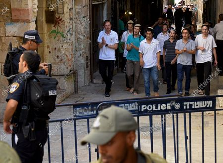 Israeli settlers chant, dance and give the victory sign after leaving the Temple Mount, or Al-Aqsa Mosque compound in Jerusalem's Old City, September 22, 2015.Israeli border police guard  Muslim women, from the Mourabitat group, not seen, as they shout slogans and hold the Koran, Islam's holy book,  at a protest against Jewish groups visiting the Al-Aqsa Mosque compound and for being banned from their holy site in the Old City of Jerusalem, September 22, 2015. Israeli Defense Minister Moshe Ya'alon outlawed the group of women and issued an order to forbid the Mourabitat group to enter the compound in Jerusalem's Old City that Muslim's call the Noble Sanctuary, or Al-Aqsa, and the Jews call the Temple Mount.