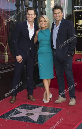 Matt Bomer (L-R), Kelly Ripa and Ted McGinley pose for photographers at a ceremony where Ripa receives the 2,561st star on the Hollywood Walk of Fame in the Hollywood section of Los Angeles on October 12, 2015.