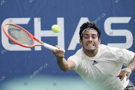 Stock Picture of Cristian Garin, of Chile, returns a shot to Norbert Gombos, of Slovakia, during the first round of the US Open tennis championships, in New York
