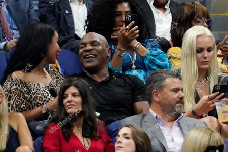 Stock Image of Former boxer Mike Tyson, center, and skier Lindsey Vonn, right, attend the first round of the US Open tennis championships, in New York