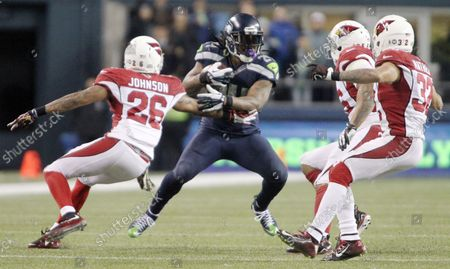 Seattle Seahawks running back Marshawn Lynch (24) can't find running room by Arizona Cardinals Rashad Johnson (26) Lamarr Woodley (56) and Tyrann Mathiew (32) at CenturyLink Field in Seattle, Washington on November 15, 2015. The Cardinals beat the Seahawks 39-32.